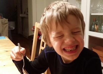 En glad och lite tandlös sexåring flinar (?) upp sig för kameran