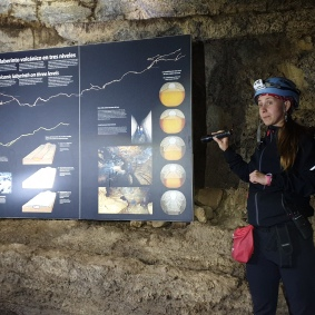 Även nere i lavagången fanns det på sina ställen samma instruerande infografik som på besökscentret. Vår guide Augustine berättar om hur lavagångar bildas, samtidigt som vi sitter och vilar på kanten av en.